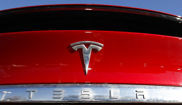 FILE - In this Feb. 2, 2020 file photograph, the company logo sits on an unsold 2020 Model X at a Tesla dealership in Littleton, Colo. Shares of Tesla Inc. fell 4% in early trading Thursday, Feb. 13, after the electric vehicle and solar panel maker said it would sell more than $2 billion worth of additional shares. The move comes just two weeks after CEO Elon Musk said the company had enough cash to fund its capital programs and it didn't need to raise any more money. (AP Photo/David Zalubowski, File)