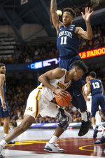 Minnesota forward Eric Curry (24) goes low as he drives to the basket against Penn State forward Lamar Stevens (11) during the first half of an NCAA college basketball game Saturday, Jan. 19, 2019, in Minneapolis. (AP Photo/Paul Battaglia)