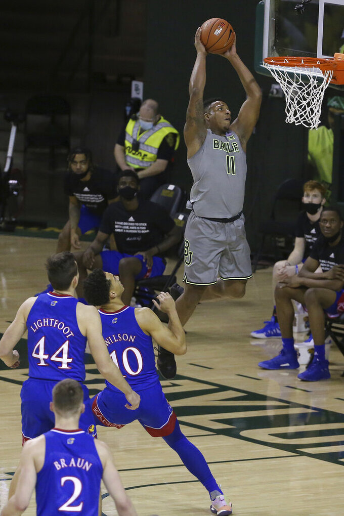 Baylor guard Mark Vital (11) scores against Kansas forwards Mitch Lightfoot (44) and Jalen Wilson (10) in the first half of an NCAA college basketball game, Monday, Jan. 18, 2021, in Waco, Texas. (AP Photo/Jerry Larson)