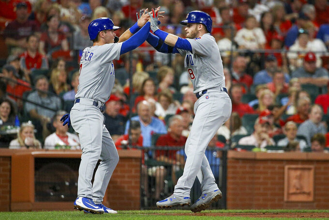 """FILE - In this Sept. 28, 2019, file photo, Chicago Cubs' Nico Hoerner, left, celebrates with teammate Ian Happ after Happ hit a two-run home run during the third inning of a baseball game against the St. Louis Cardinals in St. Louis. When the coronavirus pandemic stopped spring training last month, Ian Happ offered Nico Hoerner, Zack Short and Dakota Mekkes a place to stay if they wanted to remain in Arizona. That's how """"The Compound"""" was born. (AP Photo/Scott Kane, File)"""