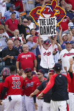 A Cleveland Indians fan holds up a sign as the team celebrates after defeating the Kansas City Royals in a baseball game, Monday, Sept. 27, 2021, in Cleveland. Cleveland played its final home game against the Royals as the Indians, the team's nickname since 1915. The club will be called the Cleveland Guardians next season. (AP Photo/Tony Dejak)