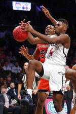 Auburn center Austin Wiley (50) and Richmond forward Nathan Cayo (4) go after a loose ball beneath Auburn's basket in the second half of an NCAA college basketball game in the Legends Classic, Tuesday, Nov. 26, 2019, in New York. Auburn defeated Richmond 79-65. (AP Photo/Kathy Willens)