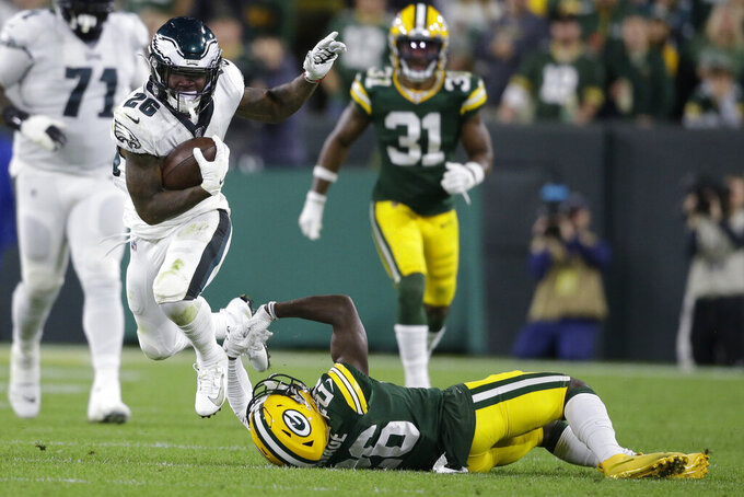 Philadelphia Eagles running back Miles Sanders is tripped by Green Bay Packers defensive back Darnell Savage after a long run during the second half of an NFL football game Thursday, Sept. 26, 2019, in Green Bay, Wis. (AP Photo/Jeffrey Phelps)