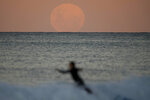 A surfer falls off his board as the moon rises in Sydney Wednesday, May 26, 2021. A total lunar eclipse, also known as a Super Blood Moon will take place later tonight as the moon appears slightly reddish-orange in colour. (AP Photo/Mark Baker)