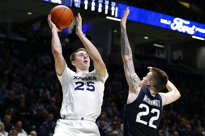 Xavier forward Jason Carter (25) shoots over Butler forward Sean McDermott (22) during the first half of an NCAA college basketball game Saturday, March 7, 2020, in Cincinnati. (AP Photo/Gary Landers)