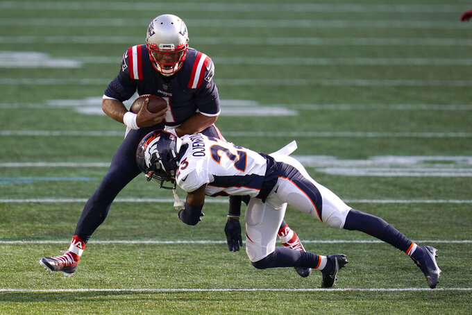 Denver Broncos cornerback Michael Ojemudia, front, tackles New England Patriots quarterback Cam Newton after catching a pass by wide receiver Julien Edelman in the second half of an NFL football game, Sunday, Oct. 18, 2020, in Foxborough, Mass. (AP Photo/Charles Krupa)