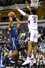 Xavier's Paul Scruggs shoots the ball against the defense of Connecticut's Isaiah Whaley in the first half of an NCAA college basketball game during the Charleston Classic Friday, Nov. 22, 2019, in Charleston, SC. (AP Photo/Mic Smith)