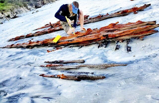 Chuck Meide, director of the Lighthouse Archeological Maritime Program in St. Augustine, takes measurements of the shipwreck that surfaced near Crescent Beach Saturday. (Colleen Michele Jones/The St. Augustine Record via AP)