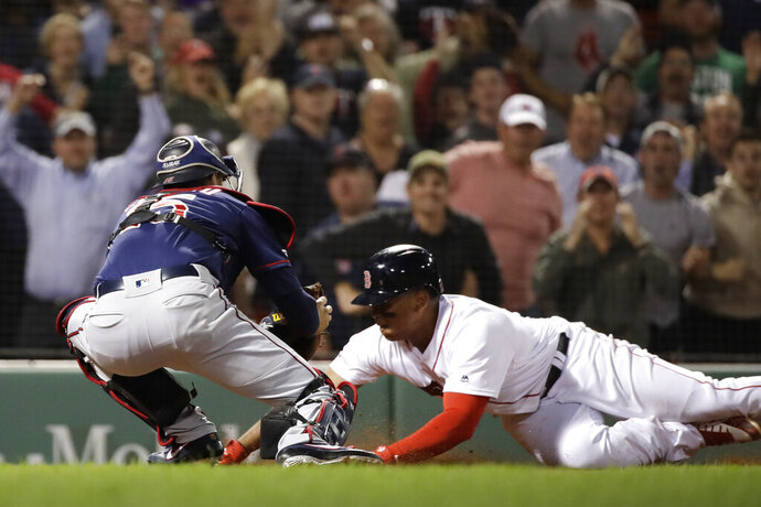 Minnesota Twins catcher Jason Castro puts the tag on Boston Red Sox's Rafael Devers at home during the ninth inning of a baseball game at Fenway Park, Thursday, Sept. 5, 2019, in Boston. The Twins won 2-1. (AP Photo/Elise Amendola)