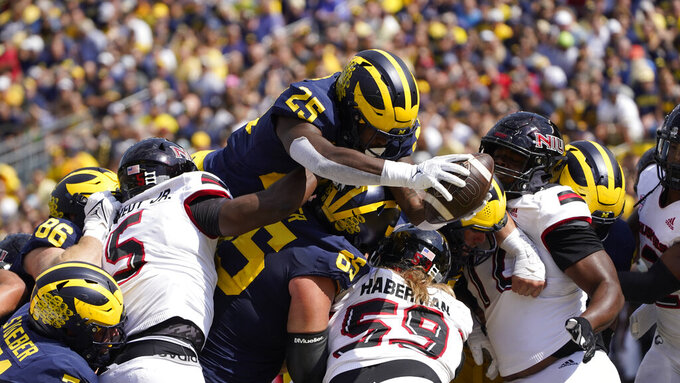 Michigan running back Hassan Haskins (25) dives over the line for a one-yard touchdown run against Northern Illinois in the first half of a NCAA college football game in Ann Arbor, Mich., Saturday, Sept. 18, 2021. (AP Photo/Paul Sancya)