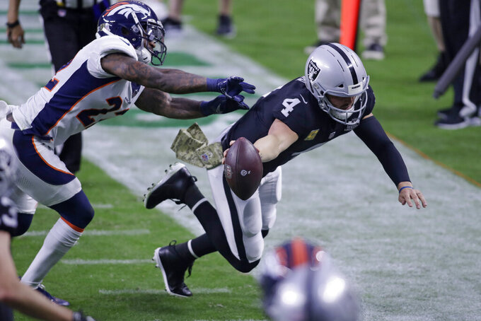 Las Vegas Raiders quarterback Derek Carr (4) runs for a gain against Denver Broncos strong safety Kareem Jackson (22) during the second half of an NFL football game, Sunday, Nov. 15, 2020, in Las Vegas. (AP Photo/Isaac Brekken)