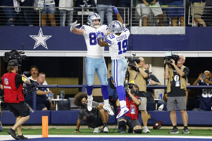 Dallas Cowboys tight end Dalton Schultz (86) and wide receiver Amari Cooper (19) celebrate a touchdown catch made by Schultz in the first half of an NFL football game against the Philadelphia Eagles in Arlington, Texas, Monday, Sept. 27, 2021. (AP Photo/Michael Ainsworth)
