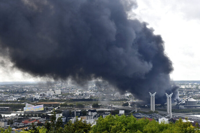 FILE - In this Sept.26, 2019 file photo, black smoke is seen after a fire broke at a chemical plant in Rouen, Normandy. Paris prosecutor said special police units are leading investigations on the site of a huge fire at a chemical plant last month in the western city of Rouen. Authorities ordered a freeze on local agricultural production and sales as a precaution while awaiting further test results. (AP Photo/Stephanie Peron, File)