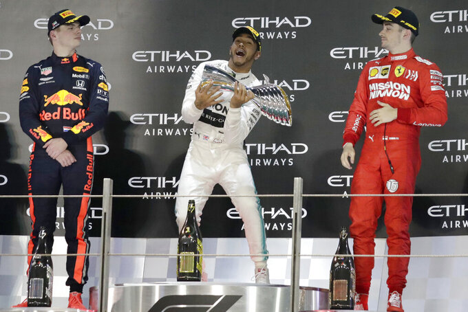 Mercedes driver Lewis Hamilton of Britain, center, celebrates on the podium with second placed Red Bull driver Max Verstappen of the Netherland's, left, and third placed Ferrari driver Charles Leclerc of Monaco after the Emirates Formula One Grand Prix at the Yas Marina racetrack in Abu Dhabi, United Arab Emirates, Sunday, Dec.1, 2019. (AP Photo/Hassan Ammar)