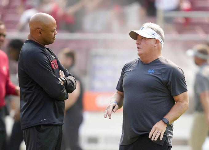 Stanford head coach David Shaw, left, talks with UCLA head coach Chip Kelly, right, before an NCAA college football game Saturday, Sept. 25, 2021, in San Francisco, Calif. (AP Photo/Tony Avelar)