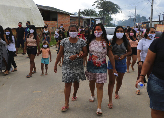 Locals walk after the funeral of Chief Messias Martins Moreira, 53, of the Kokama ethnic group, who died of Covid-19, at Parque das Tribos in Manaus, Amazonas state, Brazil, Thursday, May 14, 2020. (AP Photo/Edmar Barros)