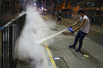 A man uses a fire extinguisher to put out a tear gas canister as they confront police in Hong Kong on Wednesday, Aug. 14, 2019. German Chancellor Angela Merkel is calling for a peaceful solution to the unrest in Hong Kong amid fears China could use force to quell pro-democracy protests. (AP Photo/Vincent Yu)