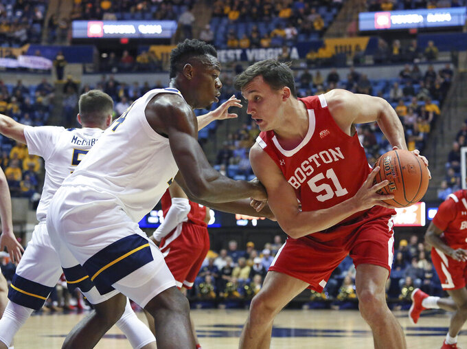 West Virginia forward Oscar Tshiebwe (34) defends against Boston University forward Max Mahoney (51) during the half of an NCAA college basketball game Friday, Nov. 22, 2019, in Morgantown, W.Va. (AP Photo/Kathleen Batten)