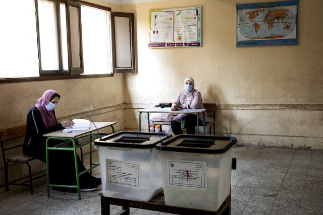 Election officials wait for people to vote on the first day of the Senate elections inside a polling station in Cairo, Egypt, Tuesday, Aug. 11, 2020. Egyptians started voting on Tuesday for the Senate, the upper chamber of parliament that was revived as part of constitutional amendments approved in a referendum last year — an election that comes as the country faces an uptick in daily numbers of new coronavirus cases. (AP Photo/Nariman El-Mofty)