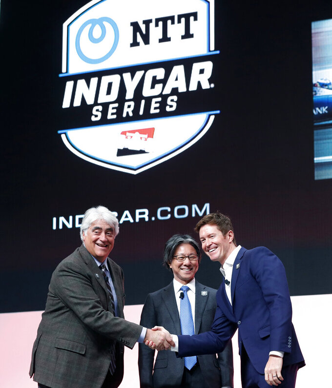 FILE - In this Jan. 15, 2019, file photo, from left, IndyCar CEO Mark Miles, Tsuneshia Okuno, an executive vice president at NTT and 2018 series champion Scott Dixon shake hands during a news conference at the North American International Auto Show in Detroit. Deals done since Scott Dixon wrapped up his fifth IndyCar championship last September include new title sponsorship from Japanese communications giant NTT, the transition to a single steady television partner in NBC Sports and a push toward expanding the grid that has made it easier for new teams to crack into the series. (AP Photo/Carlos Osorio, File)