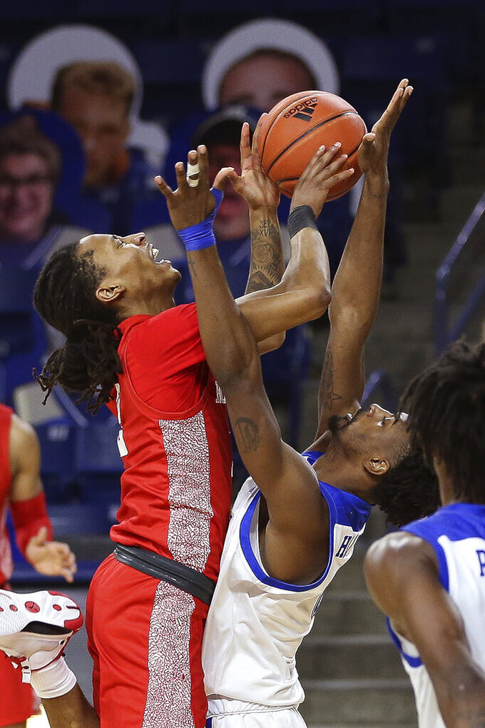 Houston's Caleb Mills, left, is fouled by Tulsa's Curtis Haywood II during the second half of an NCAA college basketball game in Tulsa, Okla., Tuesday, Dec. 29, 2020. Tulsa won 65-64. (AP Photo/Dave Crenshaw)