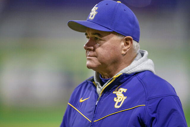 FILE - In this Feb. 14, 2020, file photo, LSU baseball head coach Paul Mainieri watches his players practice before an NCAA college baseball game against Indiana, in Baton Rouge, La. The widely praised NCAA decision to extend the eligibility of spring sports athletes who had their seasons abruptly end because of the coronavirus pandemic creates headaches for baseball and softball coaches who have to manage rosters that could become unwieldy. (AP Photo/Matthew Hinton, Fle)