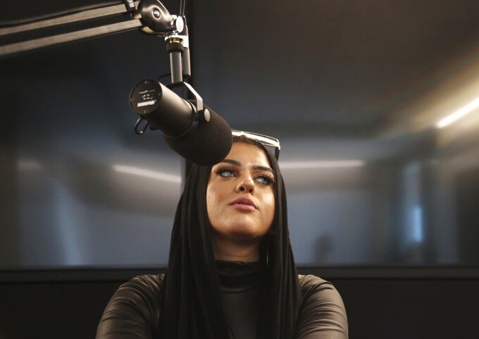 FILE - In this Dec. 19, 2019 file photo, Amani Al-Khatahtbeh, founder of Muslimgirl.com, sits in a Spotify recording studio as she and and a cohost record a pilot for her new potential podcast, in New York. After recently being threatened with Islamophobic and violent comments, the 27-year-old New Jersey congressional candidate was publicly supported by dozens of female leaders, including Congresswomen Rashida Tlaib and Ilhan Omar. (AP Photo/Jessie Wardarski, File)