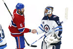 Montreal Canadiens captain Shea Weber (6) shakes hands with Winnipeg Jets goalie Connor Hellebuyck following overtime NHL Stanley Cup playoff hockey action in Montreal, Monday, June 7, 2021. (Paul Chiasson/The Canadian Press via AP)