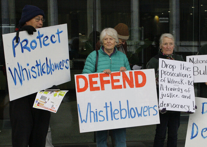 FILE - In this June 27, 2019, photo, whistleblower supporters demonstrate outside the Australian Capital Territory Supreme Court in Canberra, Australia, where former army lawyer David William McBride appeared charged with leaking secret documents to Australian Broadcasting Corp. reporters alleging misconduct in Afghanistan. Australian Broadcasting Corp. Managing Director David Anderson says he had written to Home Affairs Minister Peter Dutton calling for police to drop their investigation of two ABC reporters. (AP Photo/Rod McGuirk, File)