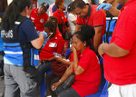 Medics attend to supporters of former Philippine First Lady Imelda Marcos outside a sports arena after falling ill during the 90th birthday celebration of the flamboyant wife of the late dictator Ferdinand Marcos Wednesday, July 3, 2019, in Manila, Philippines. Officials say more than 240 people have been brought to hospitals due to suspected food poisoning in the event which was attended by more than a thousand