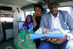 A mother and father carry their wounded child to be airlifted to the Turkish capital for treatment after they were injured in Saturday's car bomb blast in Mogadishu, Somalia, Sunday, Dec. 29, 2019.  A truck bomb exploded at a busy security checkpoint in Somalia's capital Saturday morning, killing at least 79 people including many students, authorities said. It was the worst attack in Mogadishu since the devastating 2017 bombing that killed hundreds. (AP Photo/Farah Abdi Warsameh)