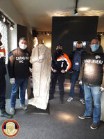 Carabinieri (Italian paramilitary police) officers of the art squad's archaeological unit pose with a headless Roman statue wearing a draped toga in Brussels on Wednesday, Feb. 3, 2021. Italian police say they have recovered a 1st century Roman statue that was stolen from an archaeological site in 2011 and found in a Belgian antiques shop by two off-duty Italian art squad police officers. The Carabinieri art squad said Monday that an Italian businessman who used a Spanish pseudonym has been referred to prosecutors for further investigation into allegations he received and then exported the statue abroad. The statue has been valued at 100,000 euro. (Carabinieri via AP)