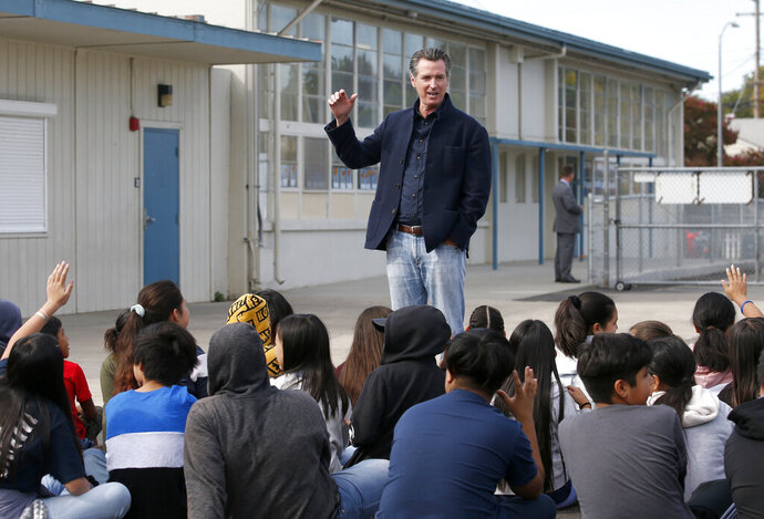 FILE - In this Monday Oct. 7, 2019 file photo, California Gov. Gavin Newsom talking to students during his visit to the Ethel I. Baker Elementary School in Sacramento, Calif. Newsom wants a three-year suspension on physical fitness tests while the state studies whether the current test for children in fifth, seventh and ninth grades can be modified or a new assessment should be drawn up. (AP Photo/Rich Pedroncelli, File )