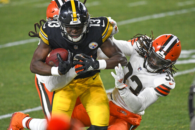 Pittsburgh Steelers wide receiver James Washington (13) is tackled by Cleveland Browns strong safety Ronnie Harrison (33) and Robert Jackson, rear, after taking a pass from quarterback Ben Roethlisberger during the first half of an NFL wild-card playoff football game in Pittsburgh, Sunday, Jan. 10, 2021. (AP Photo/Don Wright)