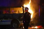 A police officer walks past a burning police vehicle on DeKalb Avenue in the Brooklyn borough of New York, Friday, May 29, 2020, after protesters gathered at Barclays Center to express anger over the death of George Floyd, a black man who died Memorial Day while in police custody in Minneapolis. (AP Photo/Frank Franklin II)