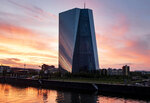 FILE - This June 22, 2019, file photo shows the European Central Bank during sunset in Frankfurt, Germany. One big reason for falling yields is purchases by central banks. The European Central Bank bought 2.6 billion euros in government and corporate bonds as part of a stimulus program that ended in December. (AP Photo/Michael Probst, File)