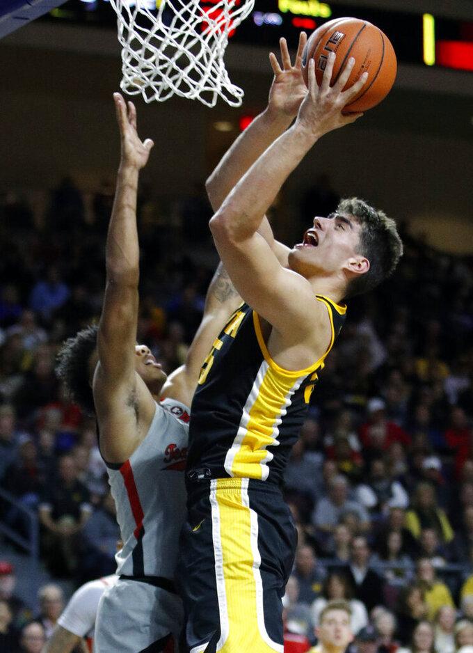 Iowa's Luka Garza (55) shoots over Texas Tech's Terrence Shannon Jr. during the second half of an NCAA college basketball game Thursday, Nov. 28, 2019, in Las Vegas. (AP Photo/John Locher)