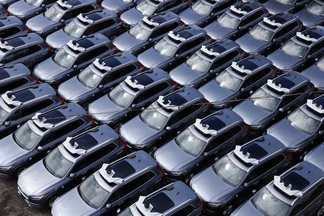 File-This March 20, 2020, file photo shows a parking lot full of Uber self-driving Volvos in Pittsburgh. Uber is selling off its autonomous vehicles development arm to Aurora as the ride-hailing company slims down after its revenues were pummeled by the coronavirus pandemic. Aurora will acquire the employees and technology behind Uber's Advanced Technologies Group in an equity transaction, the companies said Monday. (AP Photo/Gene J. Puskar, File)