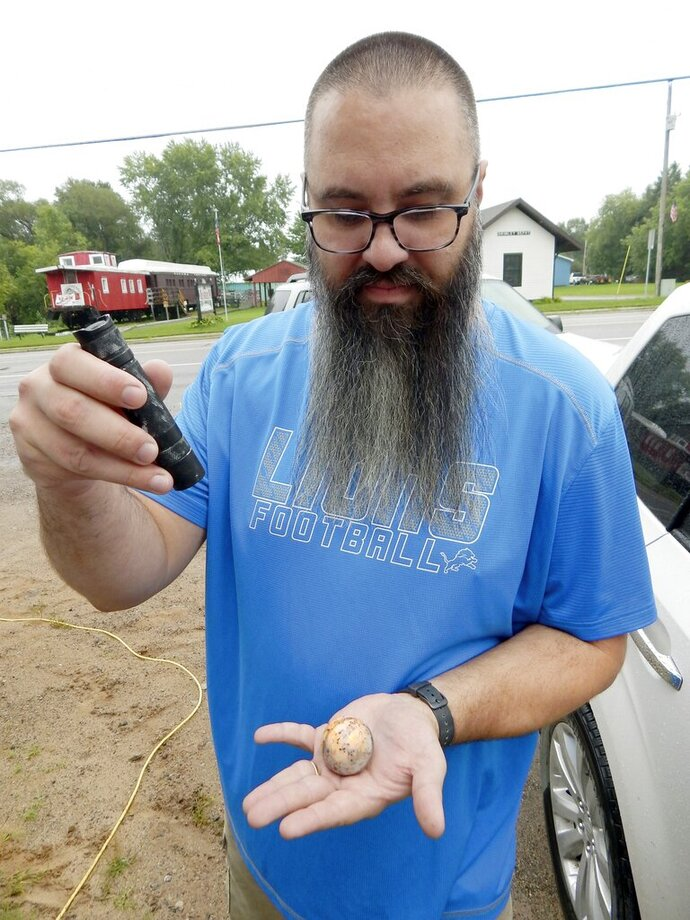 FILE- In a file photo from Sept. 4, 2018, Erik Rintamaki of Brimley, Mich., shines a UV light on a sodalite rock found along the southern shore of Lake Superior. Rintamaki collects and sells the rocks, which he's named