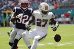 Miami Dolphins running back Kalen Ballage (27) drops a pass under pressure from New England Patriots free safety Devin McCourty (32), during the first half at an NFL football game, Sunday, Sept. 15, 2019, in Miami Gardens, Fla. (AP Photo/Lynne Sladky)