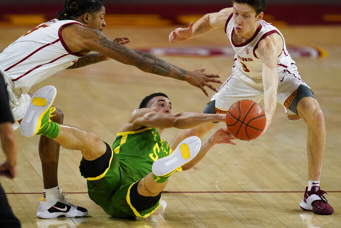 Southern California guard Isaiah White, left, guard Drew Peterson, right, and Oregon guard Chris Duarte (5) reach for a loose ball during the second half of an NCAA college basketball game Monday, Feb. 22, 2021, in Los Angeles. (AP Photo/Ashley Landis)