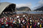 People listen to Brazil's President Jair Bolsonaro speak at an International Grace of God Church event, on Botafogo beach in Rio de Janeiro, Brazil, Saturday, Feb. 15, 2020. Tens of thousands of people gathered to celebrated the 40th anniversary of the evangelical church. (AP Photo/Leo Correa)