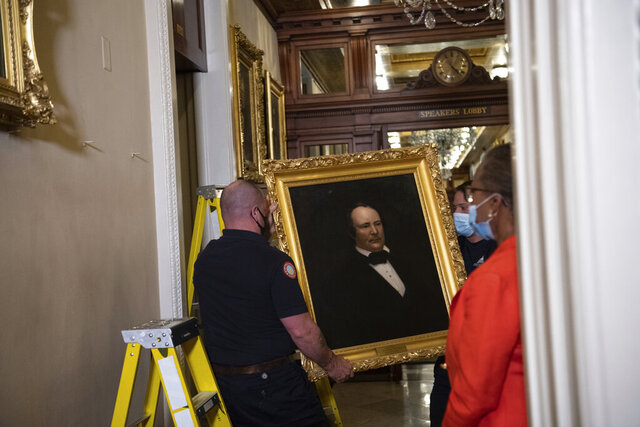 Clerk of the House Cheryl Johnson, right, watches as Architect of the Capitol workers remove a portrait of James Orr of South Carolina that was hanging in the Speakers Lobby on Capitol Hill, Thursday, June 18, 2020, in Washington. (Nicholas Kamm/Pool via AP)
