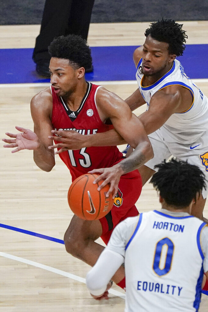 Pittsburgh's Femi Odukale, right, reaches for the ball as Louisville's David Johnson (13) drives during the second half of an NCAA college basketball game Tuesday, Dec. 22, 2020, in Pittsburgh. (AP Photo/Keith Srakocic)