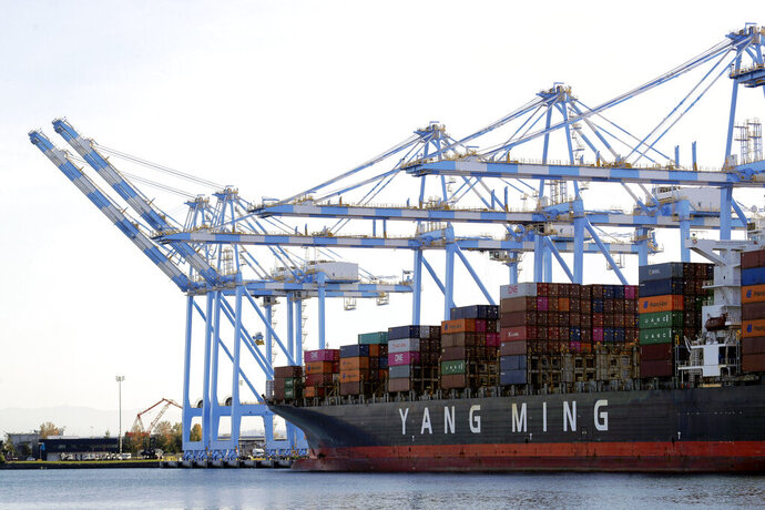 """In this Nov. 4, 2019, file photo cargo cranes are used to take containers off of a Yang Ming Marine Transport Corporation boat at the Port of Tacoma in Tacoma, Wash. President Donald Trump says he """"will make a decision very soon'' about whether to impose tariffs on imported cars and auto parts. (AP Photo/Ted S. Warren, File)"""