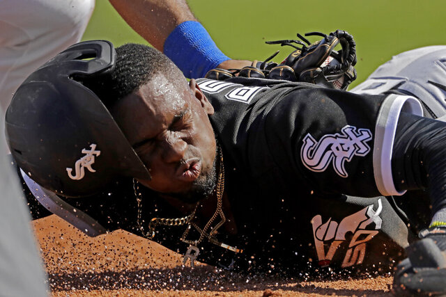 Chicago White Sox's Luis Robert is tagged by Texas Rangers third baseman Todd Frazier after sliding back to third on a double play hit into by Chicago White Sox's Adam Engel during the second inning of a spring training baseball game Saturday, Feb. 29, 2020, in Surprise, Ariz. Robert was ruled out at home on the play. (AP Photo/Charlie Riedel)