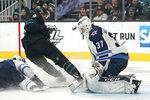 Winnipeg Jets goaltender Connor Hellebuyck (37) blocks a shot from San Jose Sharks left wing Evander Kane (9) during the third period of an NHL hockey game in San Jose, Calif., Friday, Nov. 1, 2019. The Jets won 3-2. (AP Photo/Tony Avelar)
