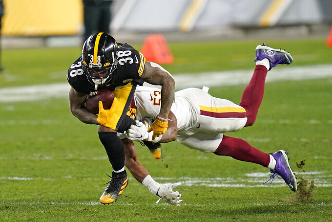 Pittsburgh Steelers running back Jaylen Samuels (38) slips a tackle-attempt by Washington Football Team inside linebacker Jon Bostic (53) during the second half of an NFL football game, Monday, Dec. 7, 2020, in Pittsburgh. (AP Photo/Keith Srakocic)