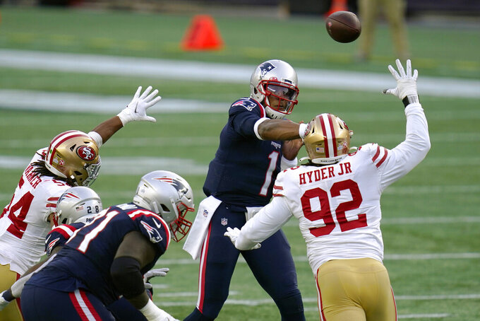 New England Patriots quarterback Cam Newton, rear, passes under pressure from San Francisco 49ers defenders Fred Warner (54) and Kerry Hyder Jr. (92) in the first half of an NFL football game, Sunday, Oct. 25, 2020, in Foxborough, Mass. (AP Photo/Charles Krupa)