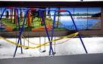 The playground at Sorensen Magnet School of Arts & Humanities in Coeur d'Alene, Idaho is wrapped in police tape to keep children off during the school closure in an attempt to stop the spread of COVID-19 on Wednesday, March 25, 2020. (Kathy Plonka/The Spokesman-Review via AP)